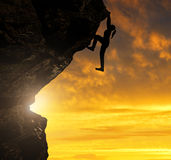 Girl climbing on rock at sunset Stock Photography