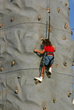 Girl Climbing Rock Wall. Young girl climbing rock wall on sunny day Stock Photography