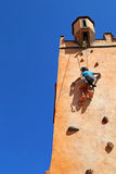 Girl climbing rock wall Stock Image