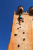Girl climbing rock wall Stock Photo