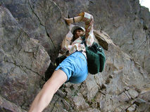 Girl climbing rocks, striving to the peak of the mountain. Looked from below stock images