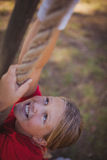 Girl climbing a rope during obstacle course training Stock Image