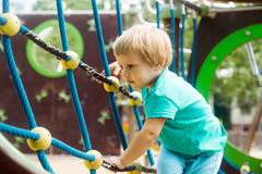 Girl climbing the ropes of challenge net. Little girl climbing the ropes of challenge net at playground stock photo