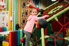 Girl climbing on a ropes, entertainment center Stock Photos