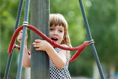 Girl climbing at ropes on playground Royalty Free Stock Photo