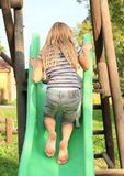 Girl climbing a slide. Barefoot girl climbing up on green slide royalty free stock images