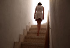 Girl climbing steps up next floor with movement. Woman walking up on stairs on a slightly movement on low exposure expressing loneliness, leftover, stress or Stock Photography