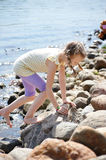 Girl climbing on stones by coast Royalty Free Stock Image