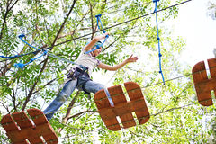 Girl is climbing to high rope structures Stock Images