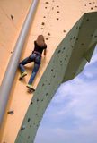 A girl climbing to the top of the wall royalty free stock image