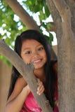 Girl Climbing Tree. Minority girl playing climbing a tree Royalty Free Stock Photo
