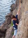 Girl climbing up a cliff. Royalty Free Stock Photography