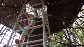 Girl climbing up the ladder on playground. Little young Caucasian girl climbing up the ladder to the cabin of a spaceship in the the big outdoor playground stock footage