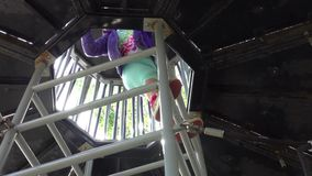 Girl climbing up the ladder on playground. Little young Caucasian girl climbing up the ladder to the cabin of a spaceship in the the big outdoor playground stock video footage
