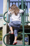 Girl climbing up a ladder Royalty Free Stock Photography