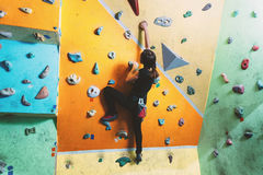 Girl climbing up on practice wall Royalty Free Stock Photo