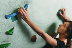 Girl climbing up on rock wall indoor Stock Photography
