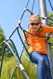 Girl climbing up the ropes. Royalty Free Stock Photography