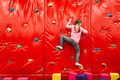 Girl climbing on a wall in attraction playground Royalty Free Stock Photo