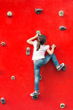 Girl climbing a wall in a playground. Girl climbing a red wall in a playground Stock Images