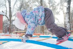 Girl climbing on winter monkey bar on snowy playground. Girl is climbing on winter monkey bar on snowy playground Royalty Free Stock Images