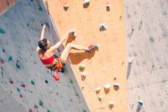 A girl climbs a climbing wall stock photos