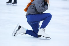Girl climbs after falling on skates stock photo