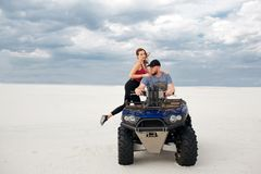 A girl climbs her boyfriend on a quad bike, they are preparing for a trip in the desert, a stylish young couple.  stock image