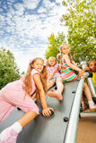Girl climbs on playground construction and mates Royalty Free Stock Photo