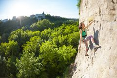 The girl climbs the rock. The girl climbs the rock against the background of a beautiful forest landscape. A woman is engaged in fitness in nature. Extreme royalty free stock photo