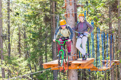 Girl climbs into ropes course. bike. Girl climbs into ropes course. Fearfully Royalty Free Stock Photo