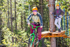 Girl climbs into ropes course. bike. Girl climbs into ropes course. Fearfully Royalty Free Stock Photos