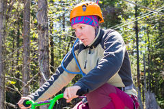 Girl climbs into ropes course. bike. Girl climbs into ropes course. Fearfully Royalty Free Stock Images