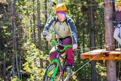 Girl climbs into ropes course. bike. Girl climbs into ropes course. Fearfully Stock Photo