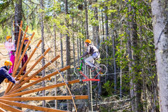 Girl climbs into ropes course. bike. Girl climbs into ropes course. Fearfully Stock Images