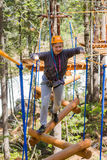 Girl climbs into ropes course. Fearfully Stock Photography