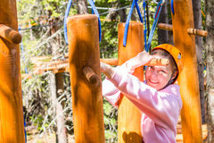 Girl climbs into ropes course. Fearfully Royalty Free Stock Images