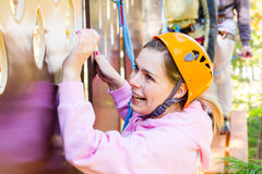 Girl climbs into ropes course. Fearfully Royalty Free Stock Image