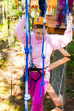 Girl climbs into ropes course. Fearfully Stock Photo