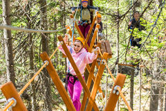 Girl climbs into ropes course. Fearfully Royalty Free Stock Photos