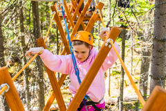 Girl climbs into ropes course. Fearfully Stock Images