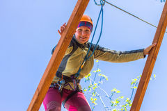 Girl climbs into ropes course. Fearfully Stock Photos