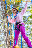 Girl climbs into ropes course. Fearfully Royalty Free Stock Photography