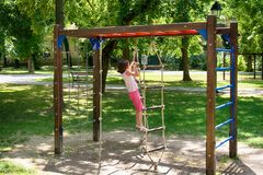 The girl climbs to the ropes.  Royalty Free Stock Photos