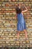 The girl climbs to the wall.  Stock Photo