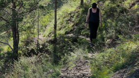 Girl climbs up the hill. A young woman goes on a forest trail in the mountains stock video
