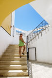 The girl climbs up the stairs in the southern resort town Stock Image