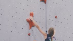 Girl climbs up on the training wall stock footage