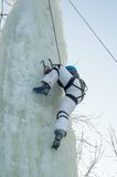 Girl climbs upward on ice climbing competition Stock Photo