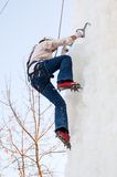 Girl climbs upward on ice climbing competition Stock Photography